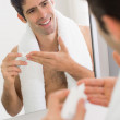 Man with reflection putting moisturizer on face — Stock Photo