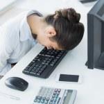 Businesswoman resting head on keyboard in office — Stock Photo #36327705