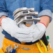 Stock Photo: Mid section of handymholding hammers with toolbelt around waist