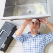 Plumber repairing washbasin drain in bathroom — Stock Photo #36328821