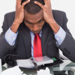 Frustrated Afro businessman with head in hands at desk — Stock Photo