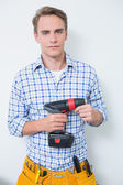 Portrait of a smiling handsome young handyman holding drill — Stock Photo