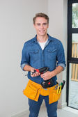 Handyman holding a drill with toolbelt around waist — Stock Photo