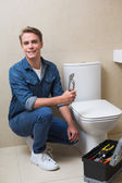 Handsome plumber with toolbox doing toilet reparation — Stock Photo