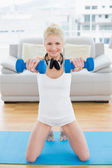 Smiling woman with dumbbells at fitness studio — Stock Photo