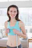 Smiling woman in sportswear measuring chest in fitness studio — Foto de Stock