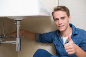 Handsome plumber gesturing thumbs up besides washbasin — Stockfoto