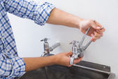 Plumber hand's fixing water tap with pliers — Stock Photo