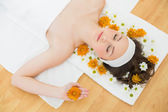 Beautiful woman with eyes closed and flowers in beauty salon — Stock Photo