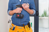 Mid section of a handyman with drill and toolbelt — Stock Photo