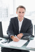 Businessman in front of computer writing document at office desk — Foto Stock