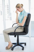 Chic businesswoman sitting exhausted on her swivel chair — Stock Photo