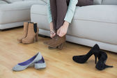 Slender young woman tying her shoelaces sitting on couch — Stock Photo