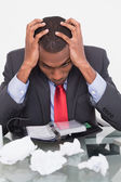 Frustrated Afro businessman with head in hands at desk — Stockfoto