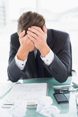 Worried businessman with head in hands at office desk — Stock Photo