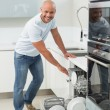 Portrait of smiling man using dish washer in kitchen — Stock Photo #36330337