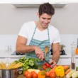Smiling young man chopping vegetables in kitchen — Stock Photo