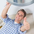 Technician gesturing thumbs up under hot water heater — Stock Photo