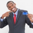Cheerful young Afro businessman pointing at credit card — Stock Photo