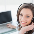 Smiling businesswoman wearing headset in front of laptop — Stock Photo #36331963