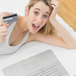 Happy young woman home shopping with her notebook — Stock Photo