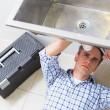 Plumber repairing washbasin drain in bathroom — Stock Photo #36333081