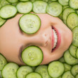 Beautiful woman with facial mask of cucumber slices on face — Stock Photo #36333219