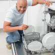 Portrait of smiling man using dish washer in kitchen — Stock Photo #36334135