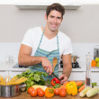 Smiling young man chopping vegetables in kitchen — Stock Photo #36334525