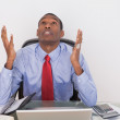 Serious Afro businessman looking up at desk — Stock Photo