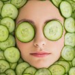 Beautiful woman with facial mask of cucumber slices on face — Stock Photo #36337085