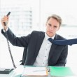 Businessman holding out phone at office — Stock Photo #36337621