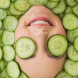 Beautiful woman with facial mask of cucumber slices on face — Stock Photo #36338145