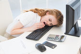 Businesswoman resting head on keyboard at office — Stock Photo