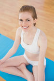 Smiling toned young woman sitting in lotus pose — Stock Photo