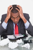 Frustrated Afro businessman with head in hands at desk — Stock fotografie