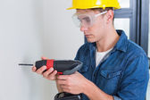Serious young handyman using a drill — Stock Photo