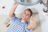 Technician gesturing thumbs up under hot water heater — Stock Photo