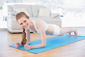 Smiling sporty woman doing push ups in fitness studio — Stock Photo