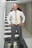 Smiling businessman standing against staircase — Stock Photo