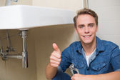 Handsome plumber gesturing thumbs up besides washbasin — Stok fotoğraf