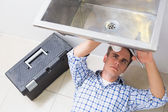 Plumber repairing washbasin drain in bathroom — Stockfoto