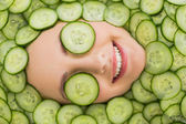 Beautiful woman with facial mask of cucumber slices on face — Stock Photo