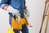 Mid section of a handyman with toolbelt and hard hat — Stock Photo