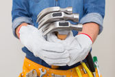 Mid section of a handyman holding hammers with toolbelt around waist — Stock Photo