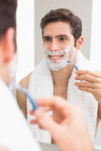 Handsome young man with reflection shaving in bathroom — Stock Photo