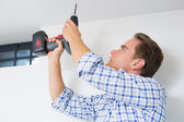Handyman using a cordless drill to the ceiling — Stok fotoğraf
