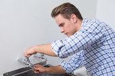 Serious plumber fixing water tap with pliers — Stock Photo