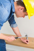 Handyman hammering nail in wooden bench — Stock Photo