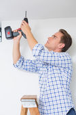 Handyman using a cordless drill to the ceiling — Stock Photo